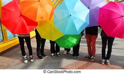 men twist colored umbrellas on bridge - young men twist...