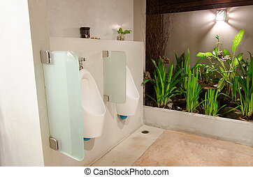 Men urinals in public toilets a row.