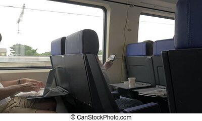 Men using cellphone and laptop in commuter train
