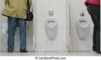 Men using urinals in supermarket toilet, time lapse