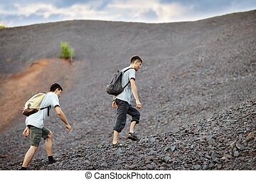 Men walks on stones slope