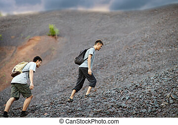 Men walks on stones slope