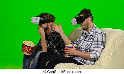 Men watch a movie in VR masks. Green screen