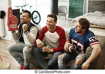 Men watching match at living room