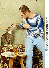 Men with a beer next to the cat steals fish