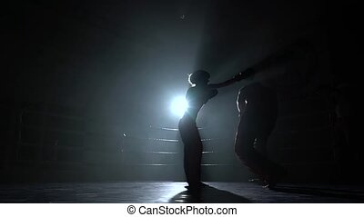 Men with a girl beating in the ring in the dark. Silhouette