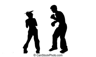Men with a girl in helmets and boxing gloves beating in the ring . Silhouette. White background