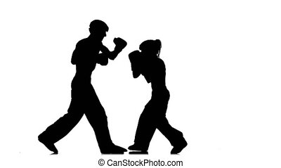 Men with a girl in helmets and kickboxing gloves beating in...