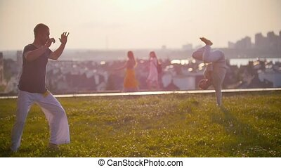 Men with a strong physique dance capoeira dance against the background of passing people and beautiful sunset, close up