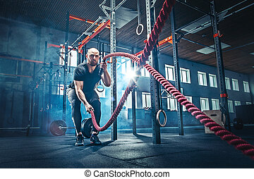 Men with battle rope battle ropes exercise in the fitness ...