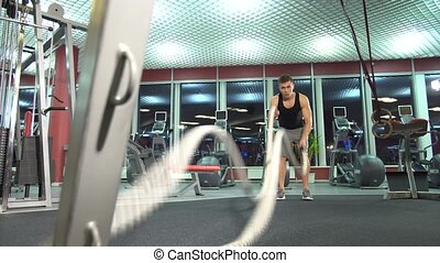 Men with battle rope in functional training fitness gym. young cute model.