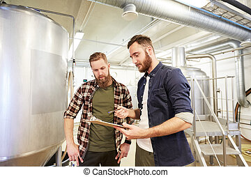 production, business and people concept - men with clipboard at brewery or non-alcoholic beer plant