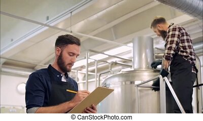 men with clipboard at brewery or beer plant - manufacture,...