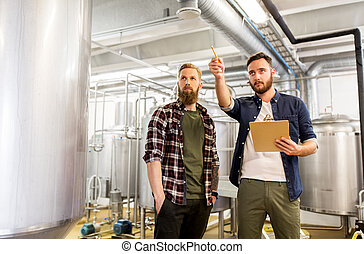 men with clipboard at craft brewery or beer plant -...