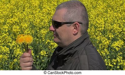 Men with dandelions near rape field