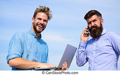 Men with laptop and smartphone solving problems using mobile internet. Workers with gadgets always having access to mobile internet. Always online. Business team works outdoor, sky background