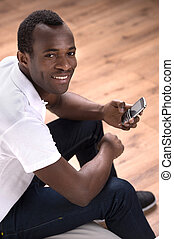 Men with mobile phone. Top view of cheerful African descent men holding a mobile phone and looking at camera