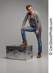 Men with mysterious box. Handsome young men stepping on the metal box and looking away while isolated on grey