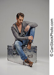 Men with mysterious box. Thoughtful young men sitting on the metal box and looking down while isolated on grey