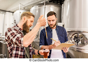 men with pipette testing craft beer at brewery - alcohol...