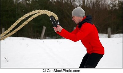 Men with rope in functional training fitness winter in a crossfit workout.