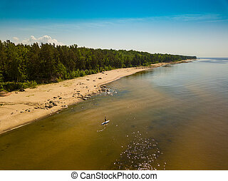 Men with supboard on the water in baltic sea.
