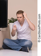 Men with TV cable. Frustrated young men holding a TV cable and looking at it with surprise
