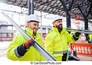 Men workers walking outdoors on construction site, working.