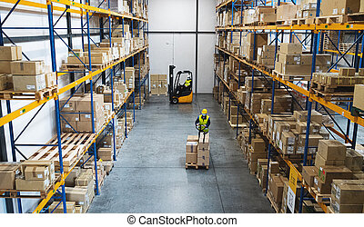 Men workers with forklift and pallet truck working indoors in warehouse, coronavirus concept.