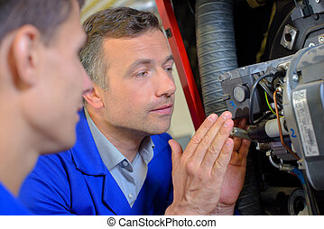 men working on a boiler