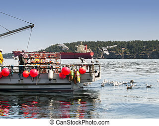 Men working on crab boat - A crab boat with crabbers and...