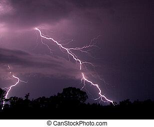 Bolts of lightning cross the purple night sky