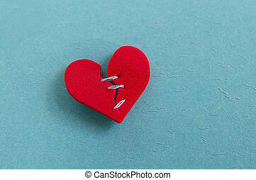 small red heart, broken with threaded stitches