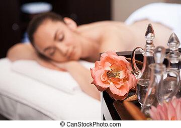 menina, é, deitando, ligado, massagem, tabela., flor, e, garrafa, ligado, tabela