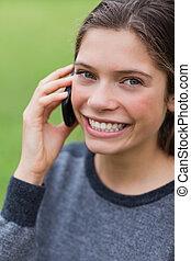 menina adolescente, falando, com, dela, cellphone, enquanto, olhar, direito, em, a, câmera