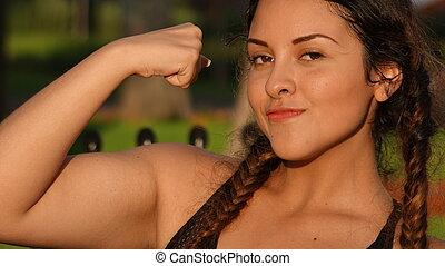 menina adolescente, músculos, flexionar
