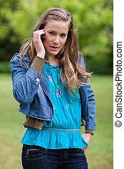 menina adolescente, usando, dela, telefone móvel, enquanto, olhando câmera
