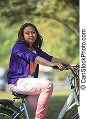 menina asiática, bicicleta equitação, em, público