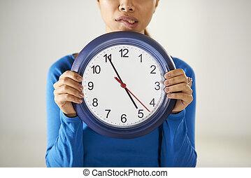 menina asiática, segurando, grande, azul, relógio, com, tensão