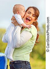menina bebê, beijando, segurando, dela, feliz, mãe