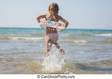 menina, corridas, banhar, em, a, mar, foco, ligado, um, pulverizador água