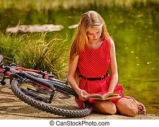 menina, em, ciclismo, livro leitura, perto, bicicleta, em, parque, outdoor.