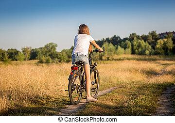 menina, em, shorts, e, t-shirt, ciclismo, em, prado, em, pôr do sol