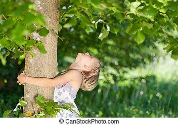 menina jovem, abraçando, um, tronco árvore