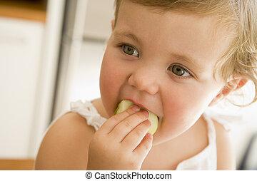 menina jovem, comendo maçã, dentro