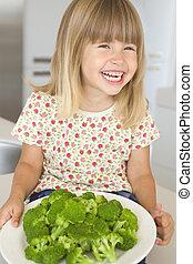 menina jovem, em, cozinha, comer, brócolos, sorrindo