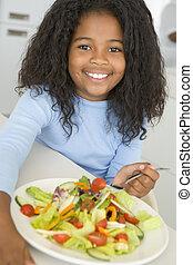 menina jovem, em, cozinha, comer, salada, sorrindo