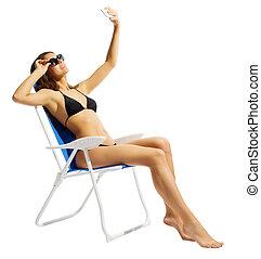menina jovem, em, swimsuite, ligado, cadeira, com, telefone móvel