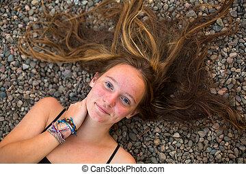 menina jovem, mentindo, ligado, a, rio, seixos, com, disperso, hair., topo, vista.