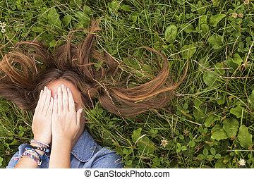 menina jovem, mentindo, ligado, grama verde, cobertura, seu, rosto, com, seu, hands.